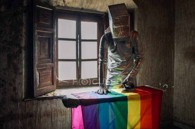 Unrecognizable person in silver costume and box on head ironing LGBTQ flag while standing in shabby abandoned room — Stock Photo