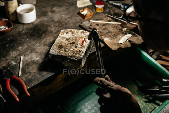 From above anonymous craftsman at workbench using hot torch and melting small pieces of metal — Stock Photo