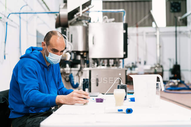 Male quality control specialist in sterile mask studying alcoholic liquid at table against professional equipment in factory — Stock Photo