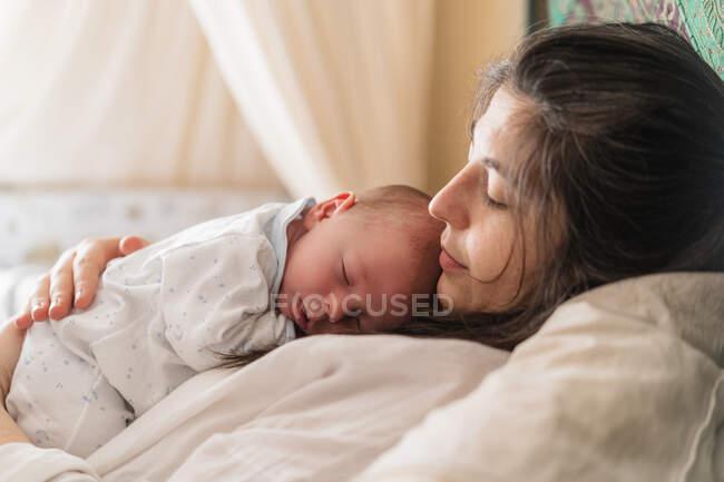 Vista lateral da mãe adulta abraçando gentilmente encantador pequena criança cochilando na casa de luz — Fotografia de Stock
