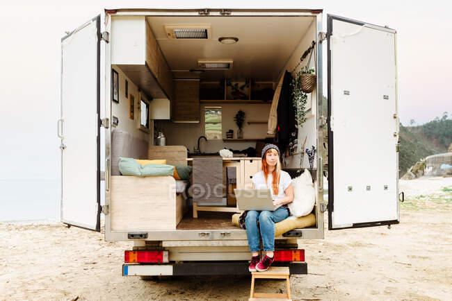 Приємна жінка - мандрівник, що сидить на сходах фургона і віддалено працює на ноутбуку. — стокове фото