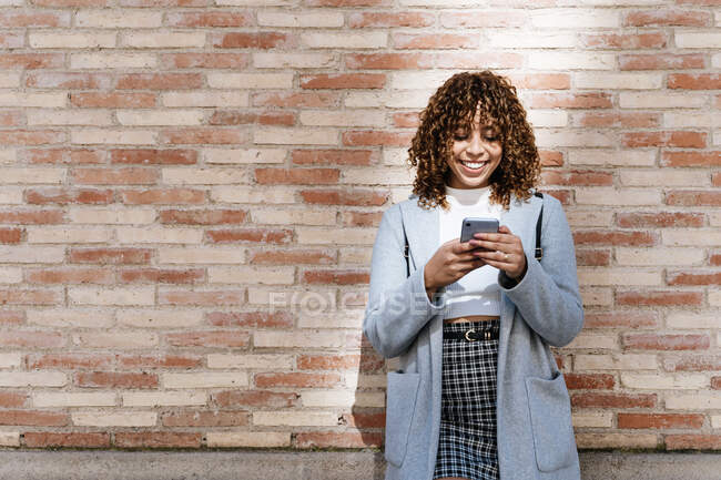 Happy young African American female with curly hair wearing blue coat browsing on mobile phone while standing against brick wall and looking away with smile — Stock Photo