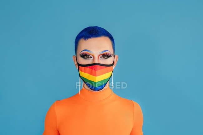 Drag queen sem emoção com cabelo azul e maquiagem provocante usando máscara protetora nas cores da bandeira do arco-íris enquanto olha para a câmera contra o fundo azul — Fotografia de Stock