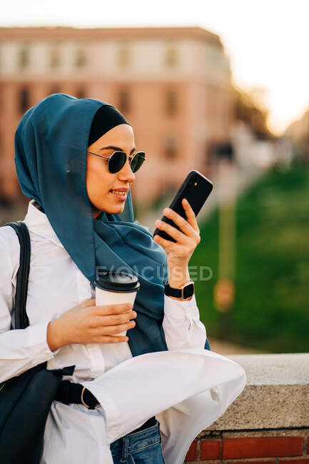 Ethnic female in headscarf and stylish sunglasses standing with takeaway drink on street and recording voice message on mobile phone — Stock Photo