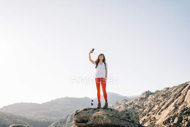 Pieno corpo di positivo giovane viaggiatore femminile con i capelli ricci scuri in abiti casual sorridente mentre prende selfie sul telefono cellulare durante il trekking in montagna nella giornata di sole — Foto stock