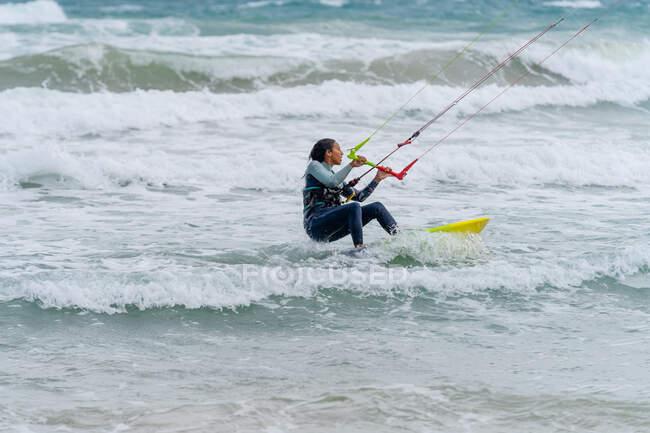 Atleta femminile attiva sul kiteboard con barra di controllo mentre pratica il kitesurf e distoglie lo sguardo sull'oceano schiumoso — Foto stock