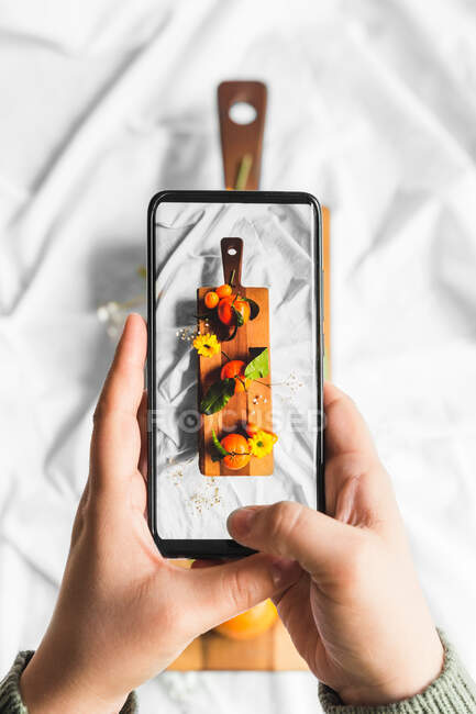 Top view of crop unrecognizable person touching screen of cellphone while taking photo of assorted tropical fruits on cutting board — Stock Photo