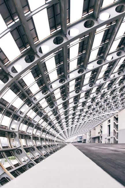 Перспективный взгляд на современный геометрический проход со стеклянными стенами в центре города — стоковое фото