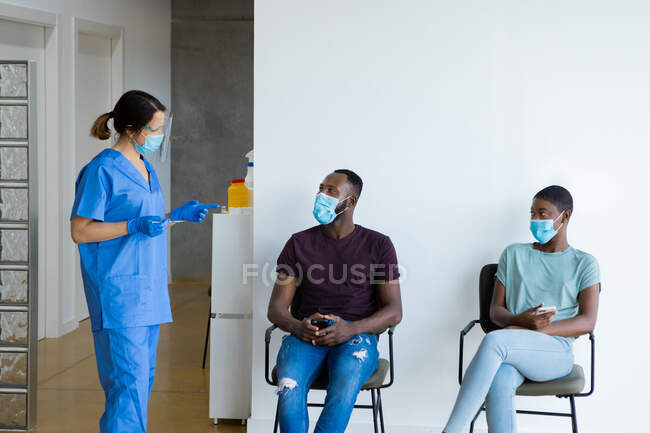 Pacientes jóvenes afroamericanos de sexo femenino y masculino que navegan en un teléfono inteligente mientras están sentados en una sala de espera hablando con una doctora en uniforme protector, guantes de látex y mascarilla antes de vacunarse en la clínica durante el brote de coronavirus - foto de stock