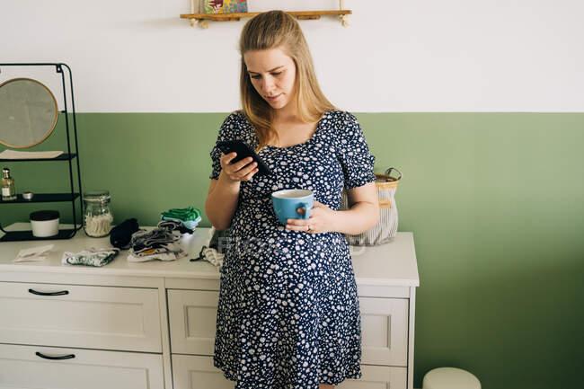 Giovane donna incinta in abbigliamento ornamentale con tazza di bevanda calda chatta sul cellulare in casa — Foto stock