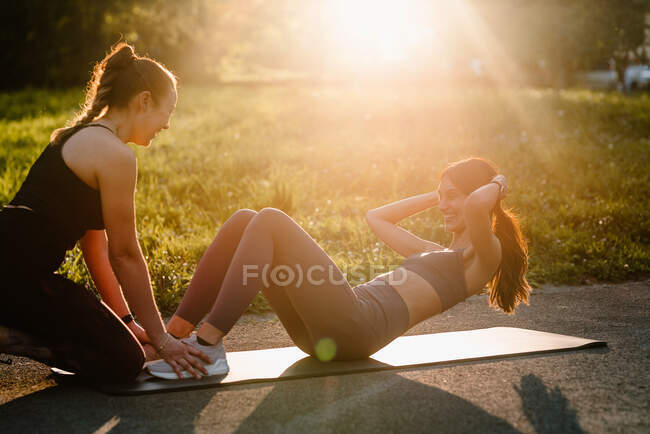 Вид сбоку на стройную спортсменку, делающую брюшные судороги с помощью спортсменки во время тренировки на закате в парке — стоковое фото