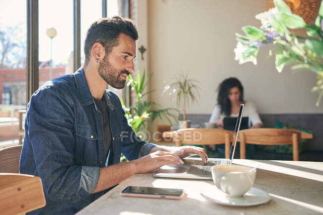 Bearded ethnic male remote employee typing on netbook at table with cup of coffee in sunlight — Stock Photo