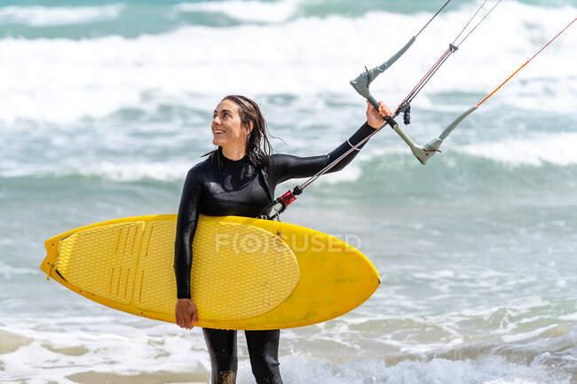 Atleta donna in muta con barra di controllo che distoglie lo sguardo sulla riva sabbiosa contro l'oceano schiumoso dopo aver praticato il kiteboarding — Foto stock