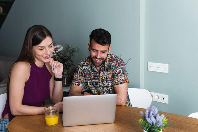 Content young couple wearing casual outfits browsing contemporary netbook together while sitting at table with glass of orange juice in living room — Stock Photo