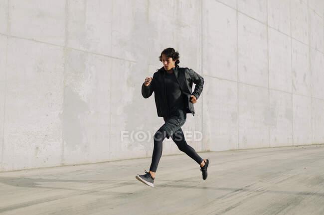 Энергичный человек в черной спортивной одежде бежит по асфальтированной дороге Индустриального района города — стоковое фото