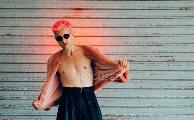 Молоді геї в сучасних сонцезахисних окулярах і стильна куртка з рожевим волоссям проти сірої стіни — стокове фото