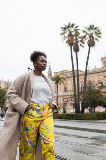 Щаслива молода афроамериканка у білій блузці, що йде по вулиці й озирається, коли тепло проводить день на міській площі. — стокове фото