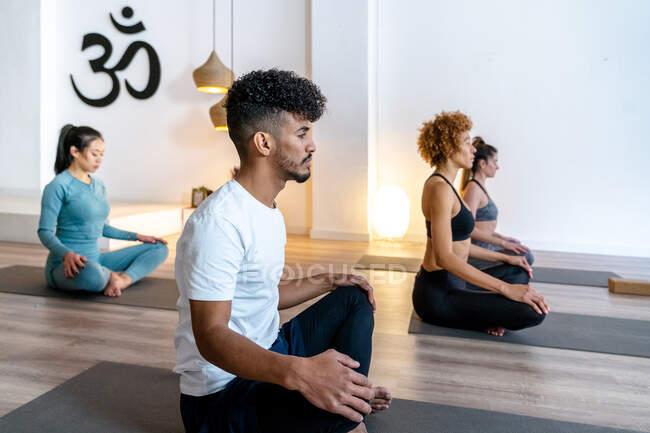Вид сбоку афроамериканца с группой разных людей, сидящих в позе Лотоса, посредничающих во время совместной практики йоги во время занятий в студии — стоковое фото