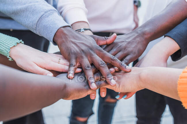 Crop unrecognizable multiethnic social justice warriors joining hands while supporting each other in BLM movement — Foto stock