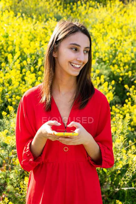 Jovem conteúdo feminino em vestuário vermelho mensagens de texto no celular contra plantas florescentes na luz solar — Fotografia de Stock