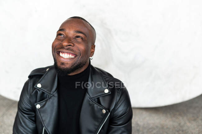 Delighted African American male in stylish leather jacket looking up and smiling happily — Stock Photo