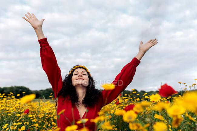 Delícia na moda fêmea em sundress vermelho e com coroa de flores de pé com os olhos fechados no campo florescente com flores amarelas e vermelhas com braços estendidos no dia quente de verão — Fotografia de Stock
