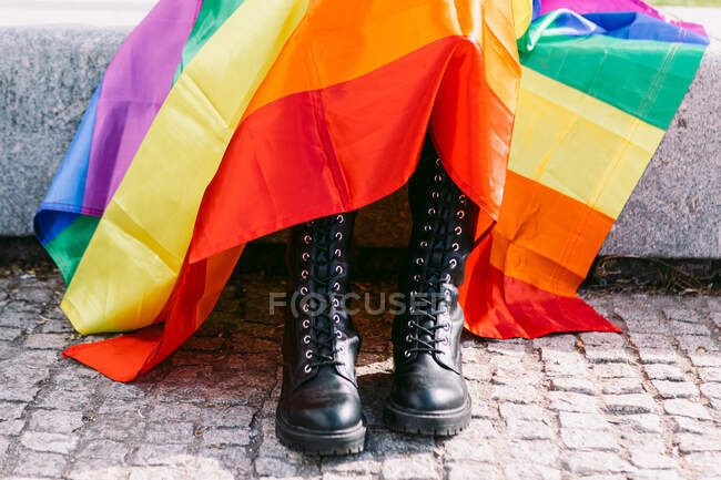 Crop unrecognizable person in black brutal boots and with rainbow LGBT flag on city street — Stock Photo