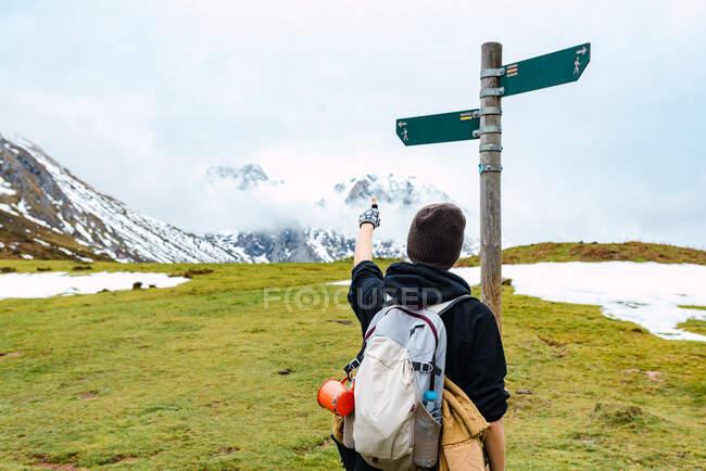 Vista posteriore dello zaino in spalla femminile che punta sulla freccia mostrando la direzione del sentiero in piedi contro il polo in Peak of Europe — Foto stock