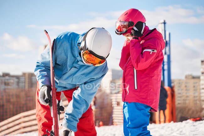 Ajuste o pai e a criança vestindo roupas esportivas quentes e capacetes colocando esquis enquanto estão em pé na colina nevada no subúrbio no inverno ensolarado — Fotografia de Stock
