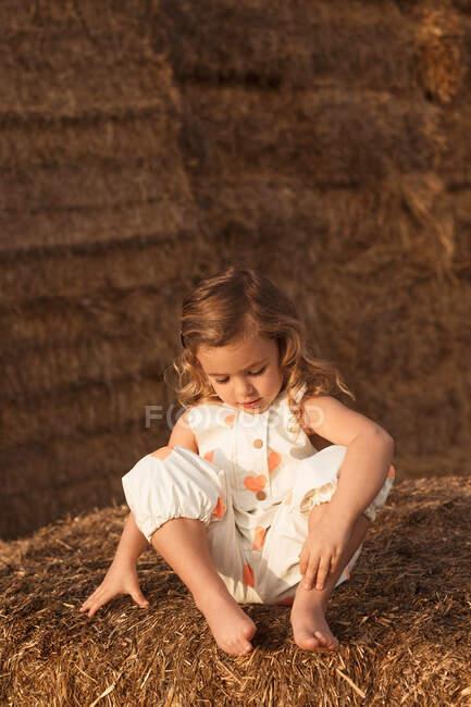 Criança adorável alegre em macacão brincando com feno sentado em fardos de palha no campo — Fotografia de Stock