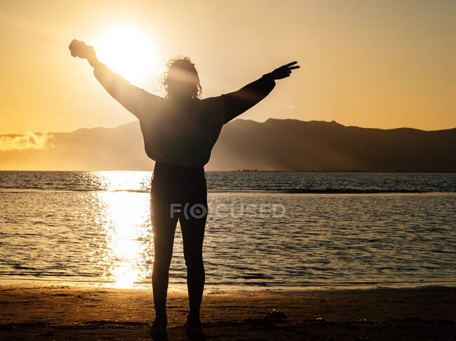 Back view silhouette of traveler with arms raised and peace gesture enjoying freedom while standing on seashore at sunset time - foto de stock
