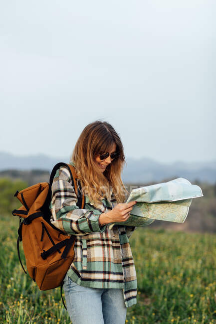 Smiling female backpacker in sunglasses watching paper guide on lawn under light sky during summer trip — Stock Photo