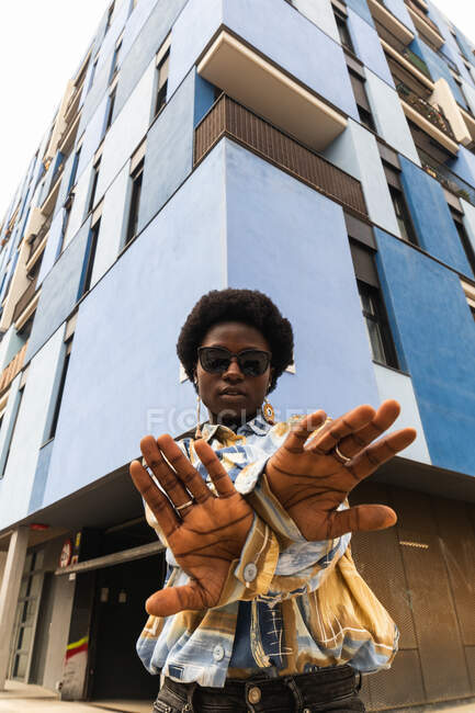 Bajo ángulo de seria joven afroamericana hembra en traje casual y gafas de sol con los brazos extendidos y cruzados de pie cerca de la esquina del edificio urbano moderno - foto de stock