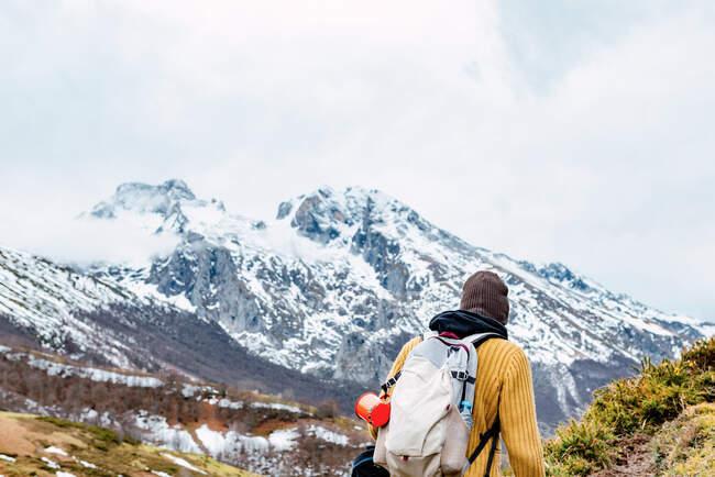 Vista posterior de turista anónimo con mochila de pie sobre césped cubierto de nieve en el valle de las montañas en los picos de Europa - foto de stock