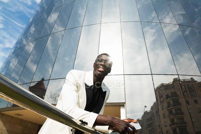 Щасливий молодий афроамериканський підприємець у стильному вбранні і окуляри з мобільним телефоном у місті в сонячний день. — стокове фото