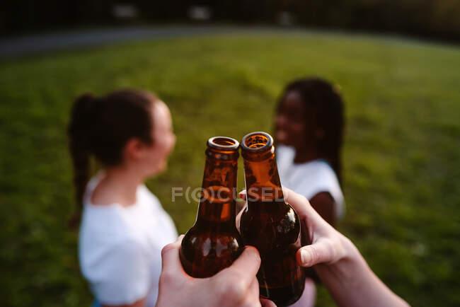 Grupo de felizes mulheres diversas que se reúnem no parque e clinking garrafas de cerveja enquanto desfrutam de fim de semana de verão juntos — Fotografia de Stock
