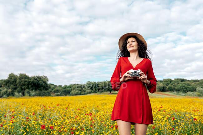 Mulher sorridente de chapéu tirando foto na câmera vintage no prado sob céu nublado — Fotografia de Stock