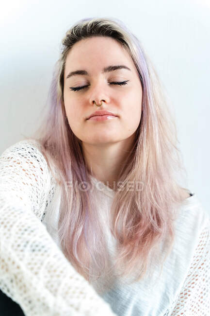 Charming young female with eyes closed in casual apparel with dyed hair on white background — стоковое фото