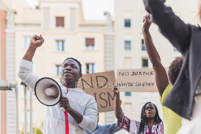 African American male screaming in megaphone during Black Lives Matter protest in city while standing in crowd of multiethnic demonstrators — Fotografia de Stock