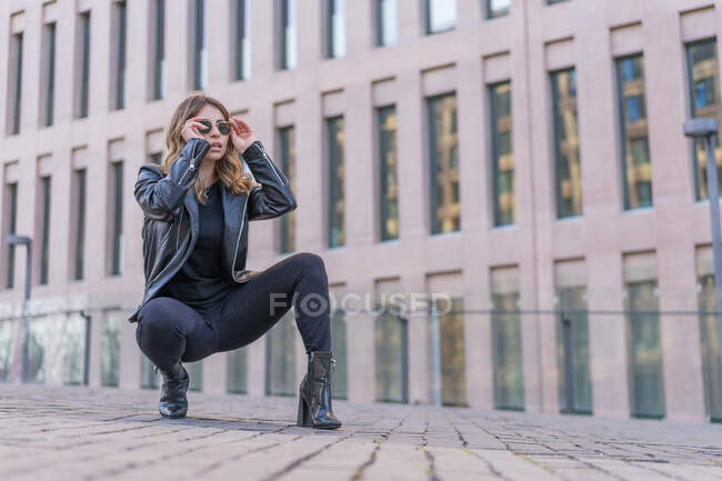 Full body of trendy female in black leather jacket and boots wearing sunglasses while sitting on haunches on pavement against modern building — Stock Photo