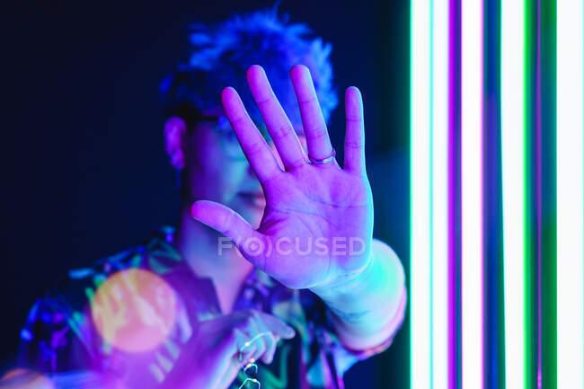 Самка в орнаментальному вбранні з витягнутою рукою демонструє захисний жест у блискучому пурпуровому світлі. — стокове фото