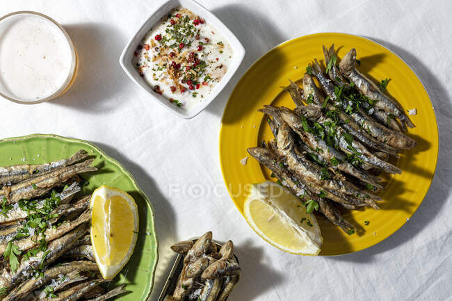 From above of traditional Spanish fried boquerones served on plates with lemons and bowl of white soup placed on table with glass of beer in restaurant — Stock Photo