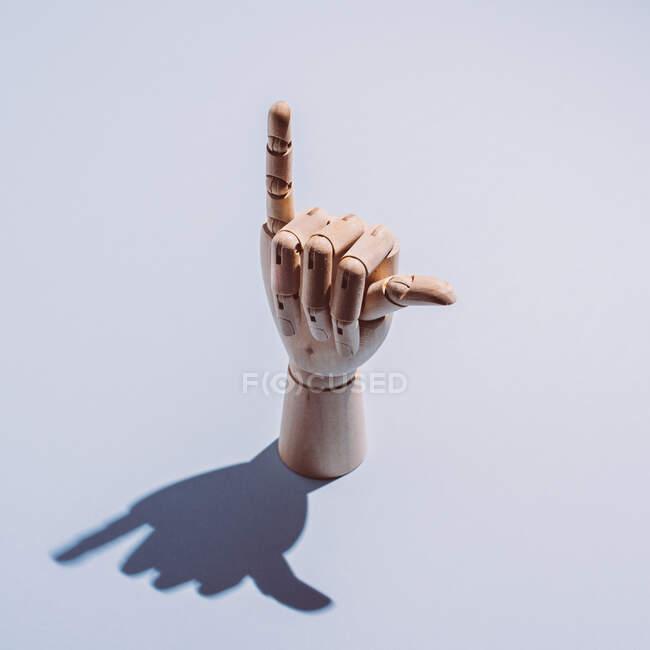Desde arriba de la mano maniquí de madera flexible decorativa que muestra el signo de shaka colocado en el fondo blanco - foto de stock