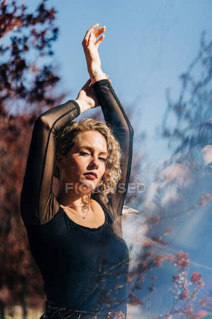 Slim elegant female standing with raised arms in garden on sunny day and looking at camera — Stock Photo