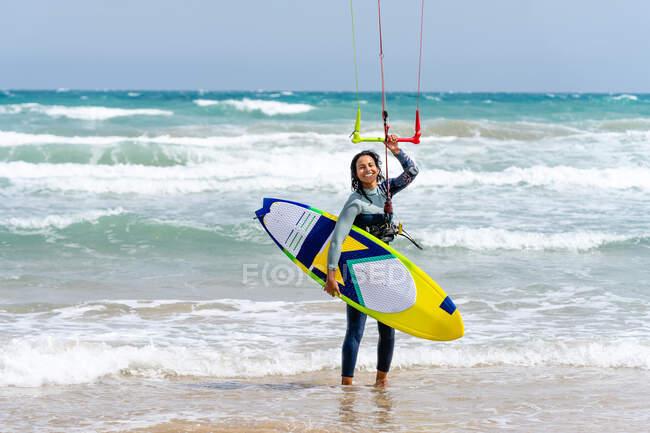 Atleta donna in muta con barra di controllo che guarda la telecamera sulla riva sabbiosa contro l'oceano schiumoso dopo aver praticato il kiteboarding — Foto stock