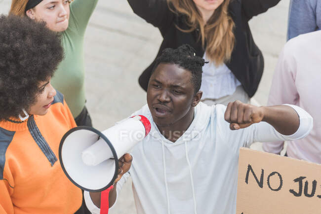 From above African American male screaming in megaphone during Black Lives Matter protest in city while standing in crowd of multiethnic demonstrators — Fotografia de Stock