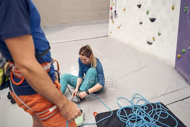 De cima da colheita instrutor masculino de pé com arnês e mulher sentada no chão e se preparando para escalar no clube de pedregulho — Fotografia de Stock
