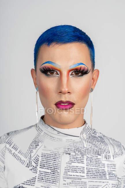 Зображення безпристрасного дивака з пофарбованим синім волоссям і провокативним гримом, дивлячись на камеру проти білої стіни. — стокове фото