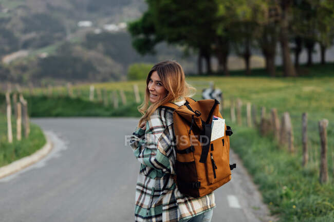 Cheerful female hiker with route map in rucksack strolling on countryside roadway against mount looking over the shoulder at camera — Stock Photo