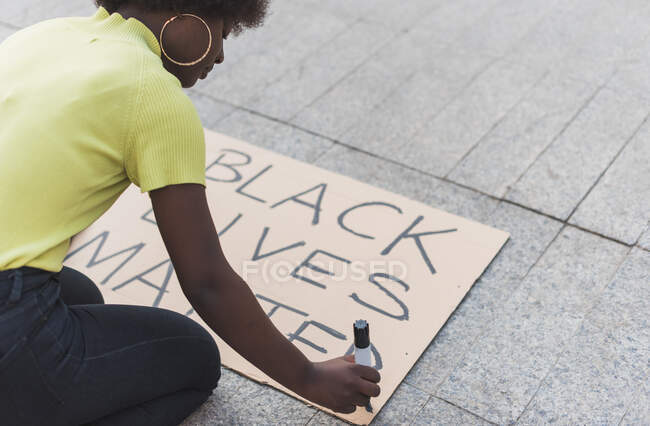 High angle side view of cropped African American female activist writing Black Lives Matter and making placard for protest against racism in city — Fotografia de Stock